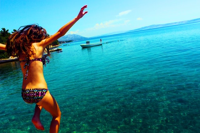 Young woman jumping into the ocean
