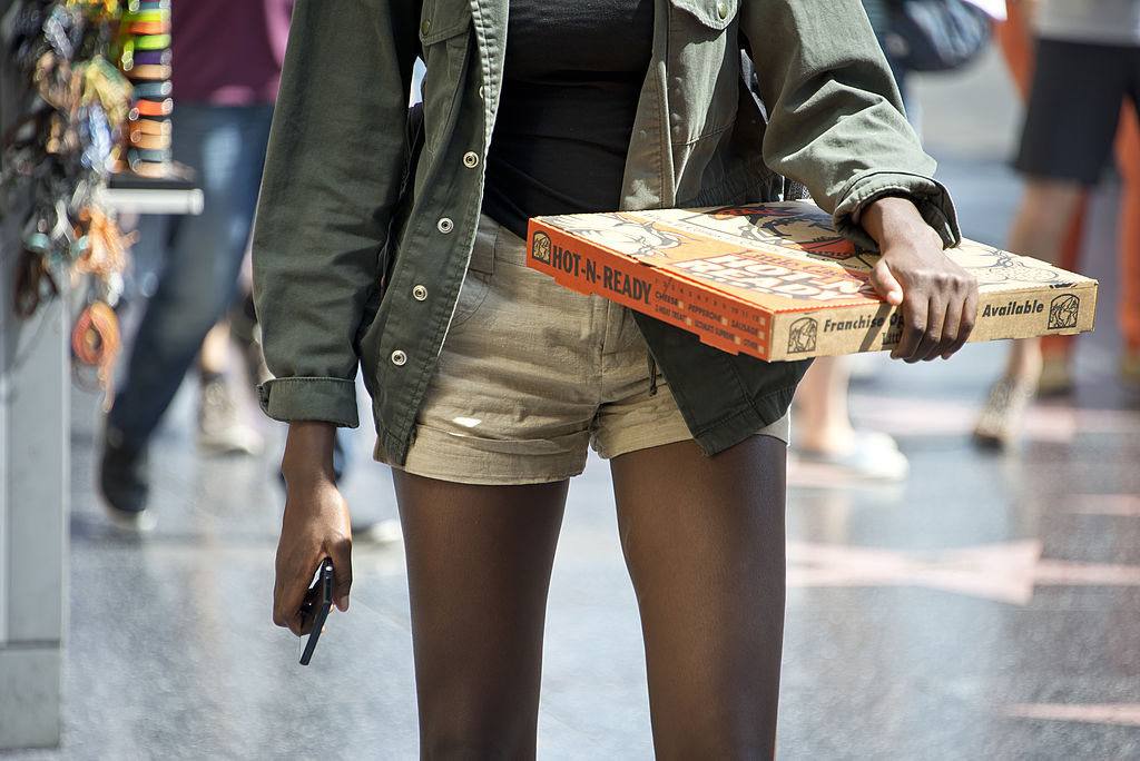 "A young woman carrying a pizza walks down Hollywood Boulevard in Hollywood, California, on September 17, 2013. It's the latest weight loss craze among American teens striving to emulate the models they see in magazines: the ""thigh gap"", in which slender legs, when standing with feet together, do not touch. AFP PHOTO / Robyn Beck (Photo credit should read ROBYN BECK/AFP/Getty Images)"