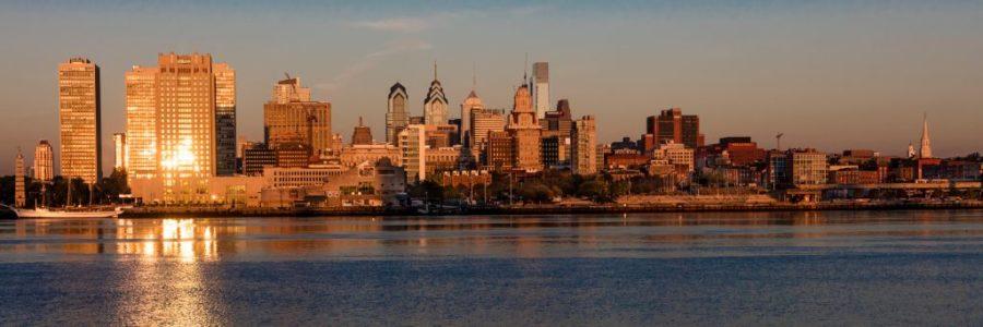 Philadelphia, PA skyscrapers and skyline at sunrise reflect golden light in Delaware River,