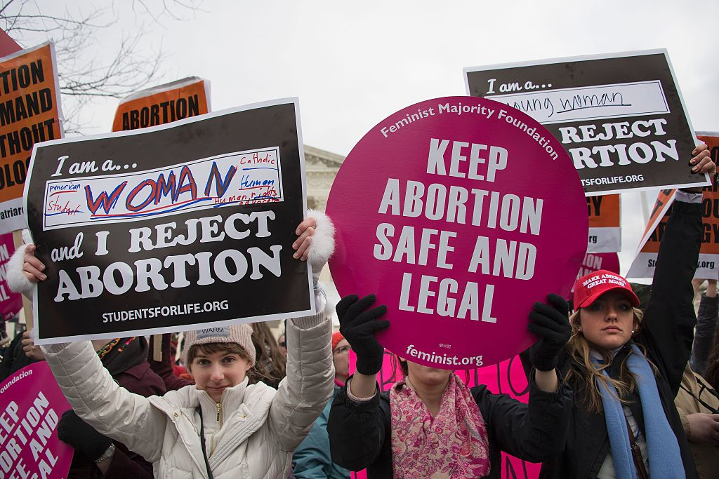 A pro-choice activist (C) demonstrates in the middle of pro-life activists as they demonstrate in front of the US Supreme Court during the March For Life in Washington, DC, January 27, 2017.