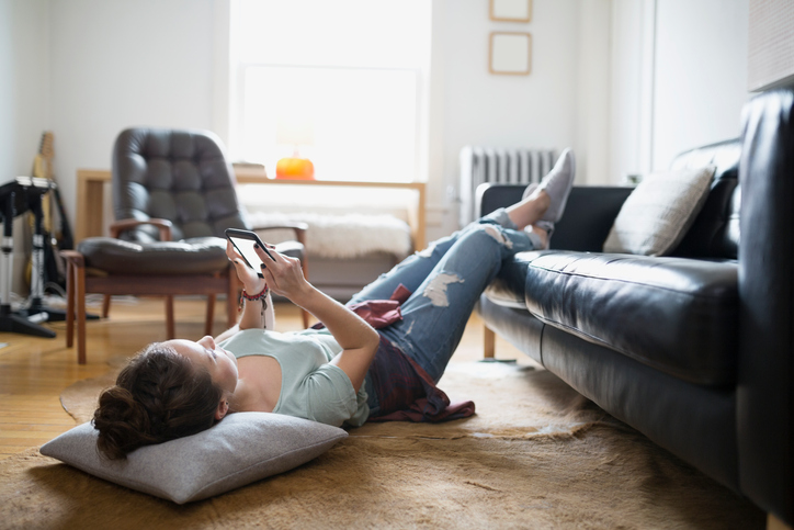 girl laying on the floor texting on a dating app.