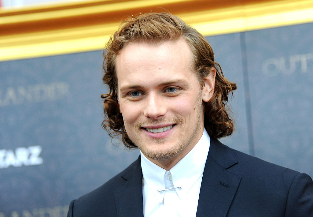 A close-up of actor Sam Heughan in a suit on the red carpet