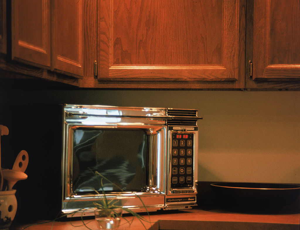 A chrome Radarange by Amana microwave oven features a keypad and digital display screen and sits on a kitchen countertop, 1970s.