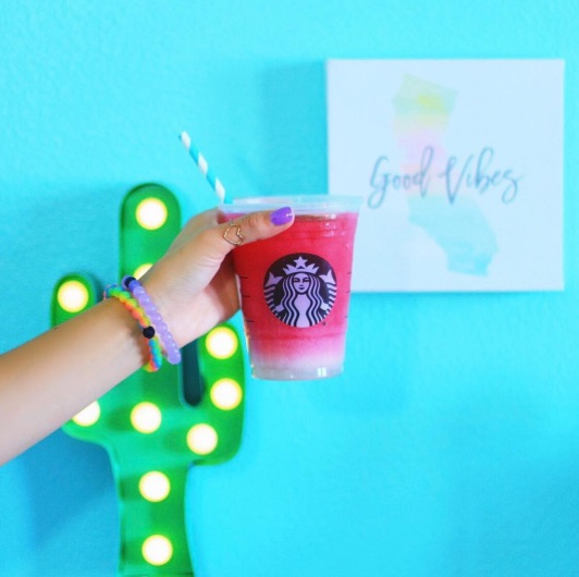A hand holds up the Starbucks Ombre Pink Drink