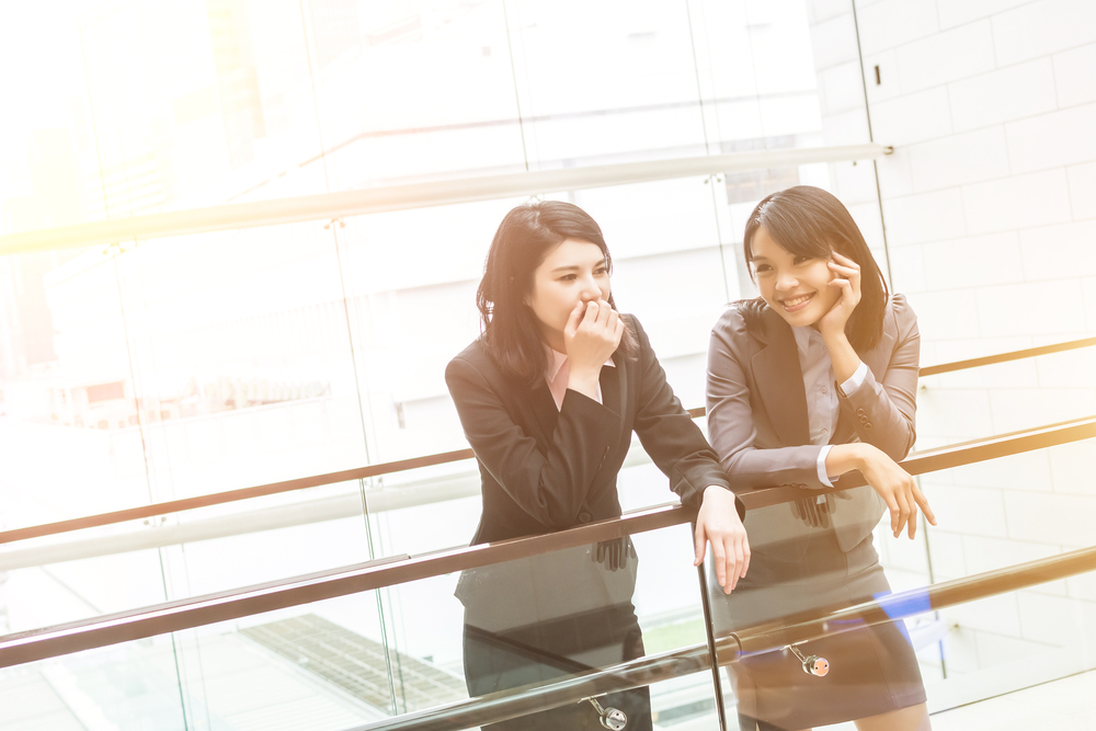 Two Asian women smiling at the office