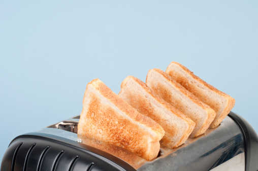 Four slices of white toast in four-slot toaster, close-up