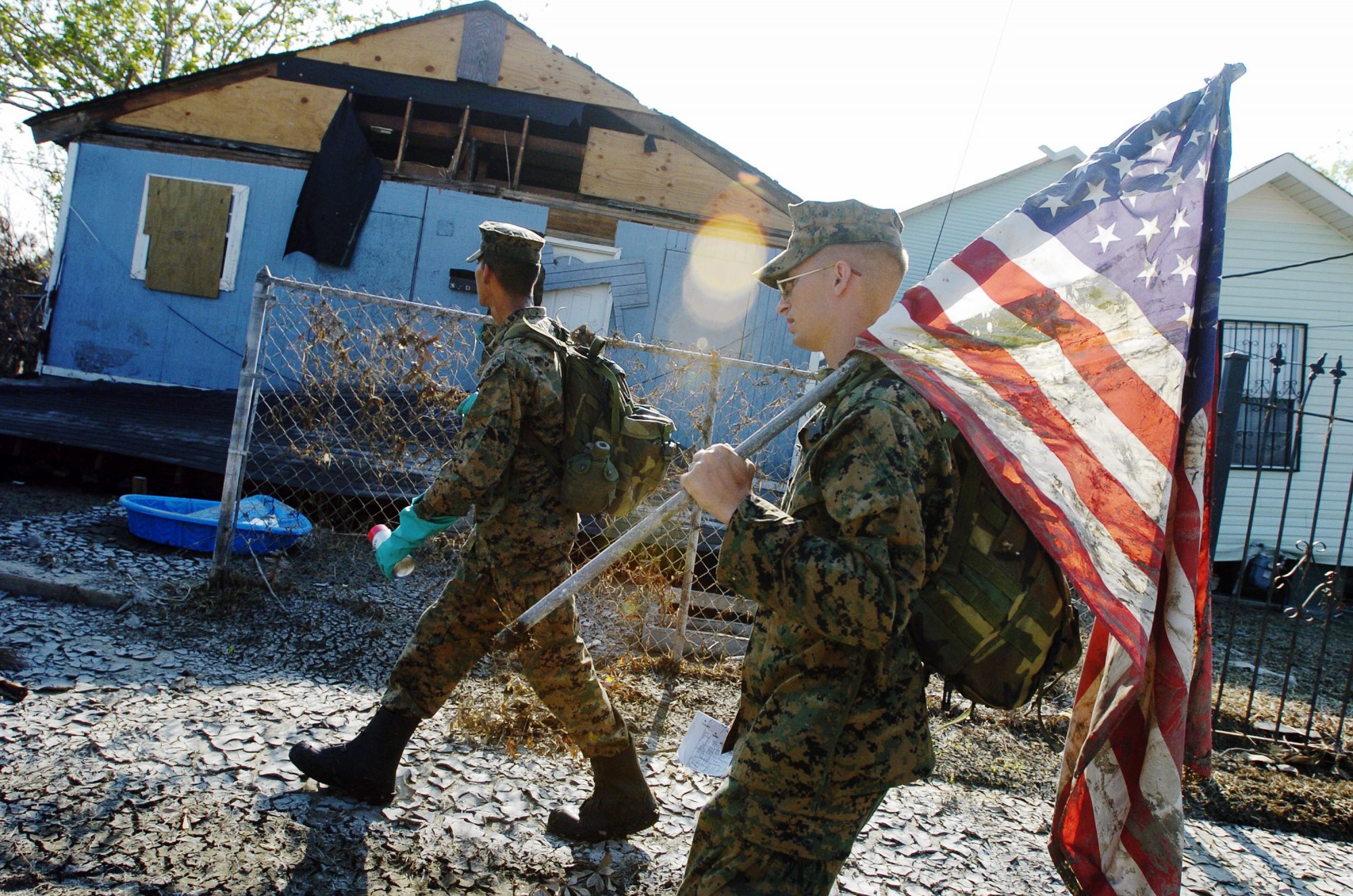 UNITED STATES - CIRCA 2002: Cpl. Karl Krebsbach carries a tattered and muddied American flag he found as he and other Marines from Camp Lejeune, N.C., patrol a Lower Ninth Ward neighborhood for a second time to search for signs of life in the aftermath of Hurricane Katrina. (Photo by Linda Rosier/NY Daily News Archive via Getty Images)
