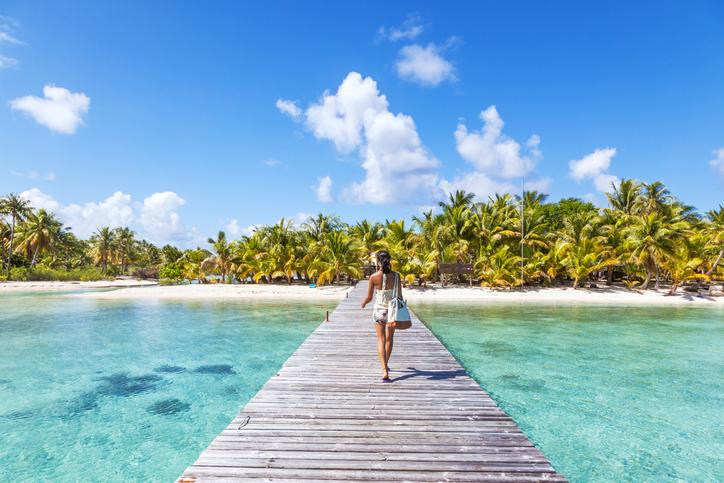 Tourist walking on jetty, Tikehau atoll, Tuamotu Archipelago, French Polynesia, Oceania