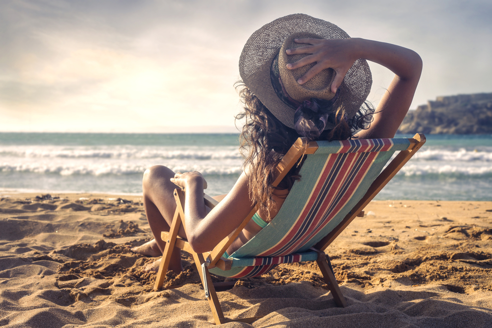 Woman at the beach sitting in a chair.