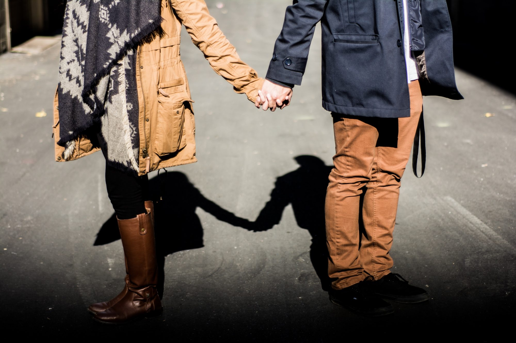 couple holding hands while facing opposite directions