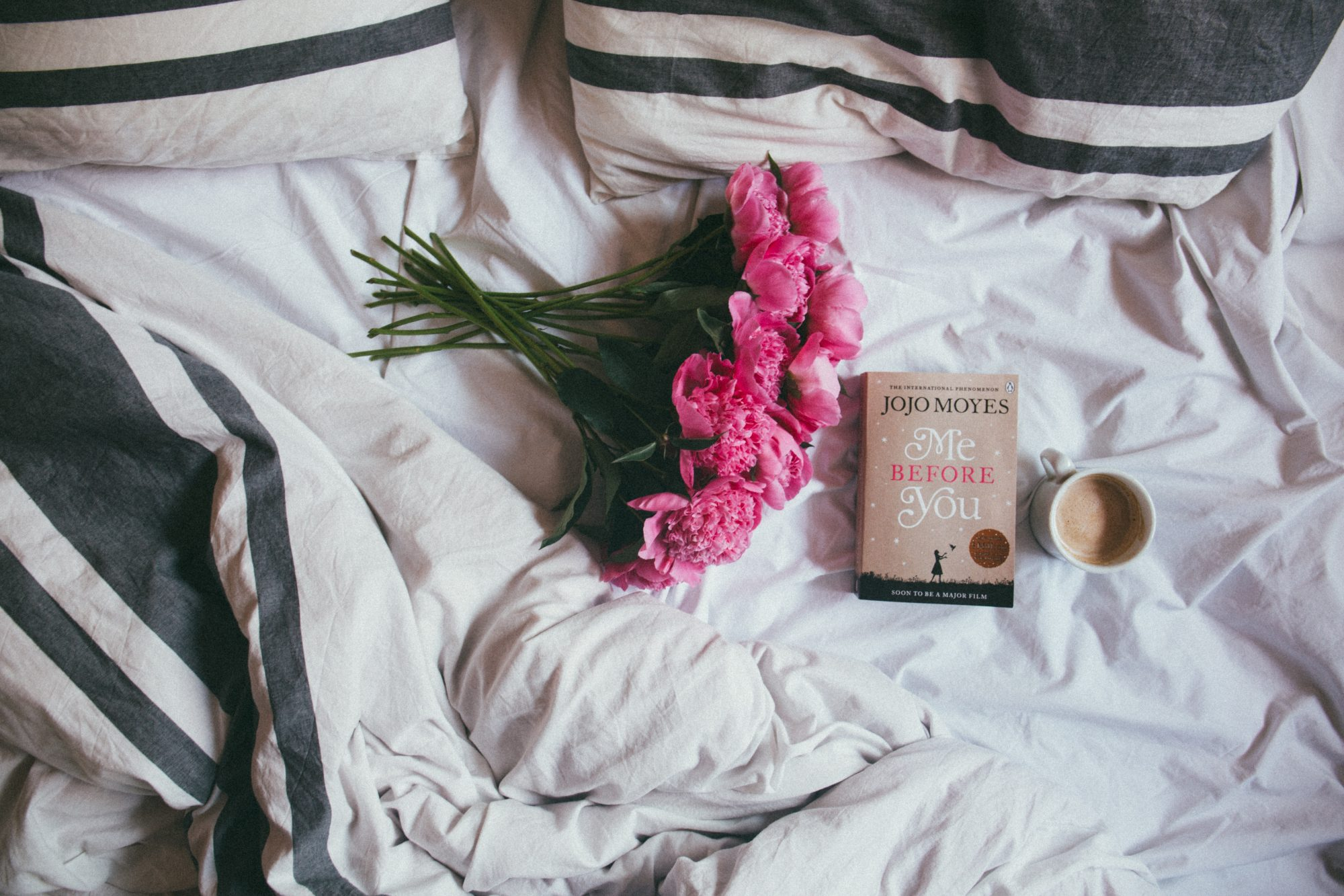 pink flowers book and cup of coffee sitting on a bed