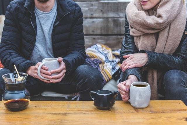 Two people talking and drinking coffee