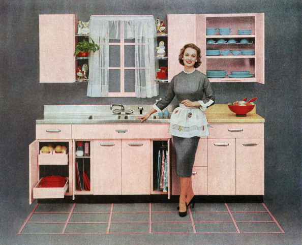A housewife stands in a pink kitchen in a vintage illustration from the 1950s