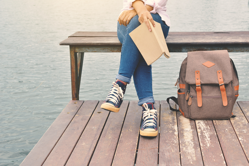 girl sitting on a bench with a book