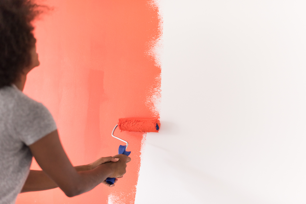 Woman painting her apartment pink.