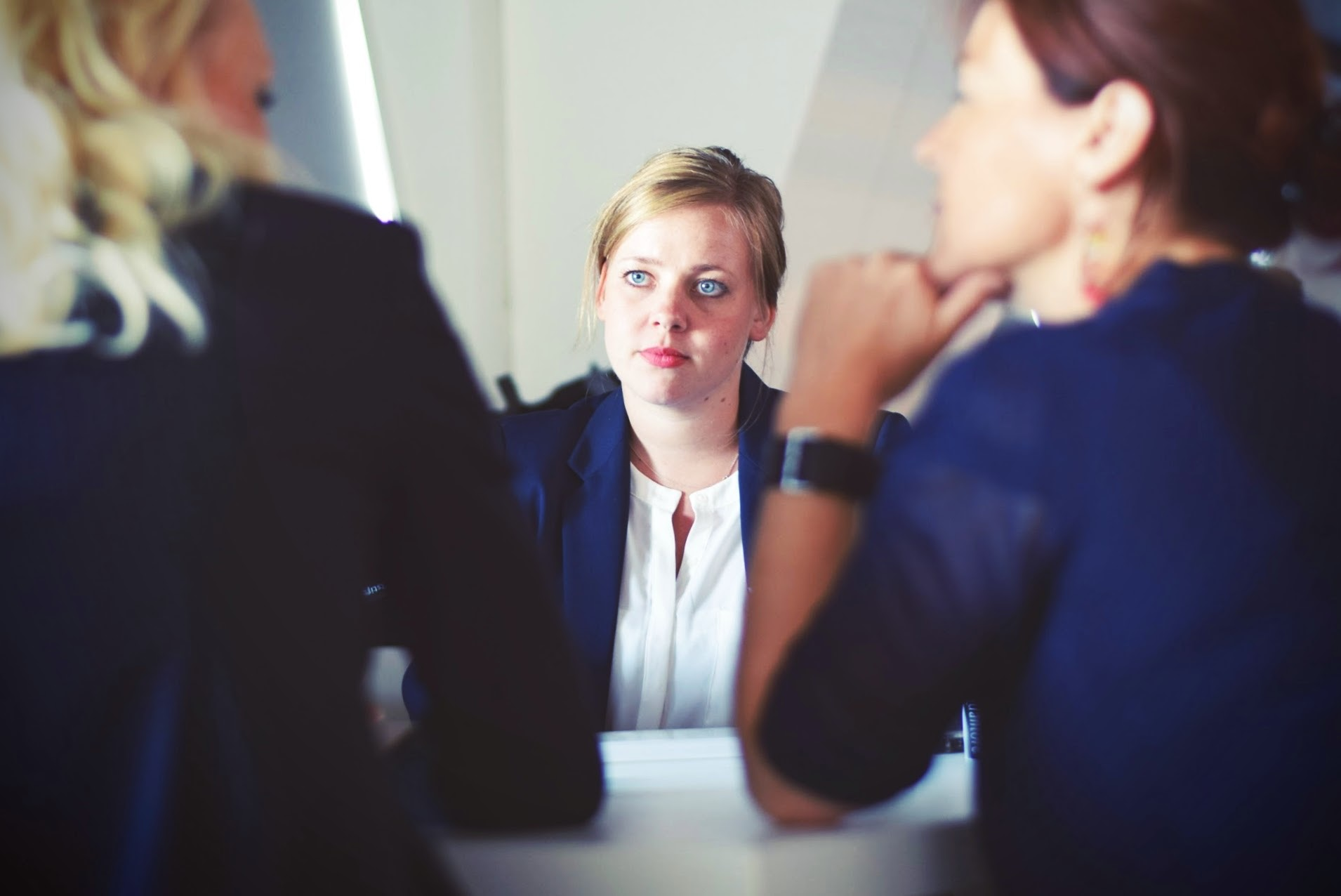 woman sits across from two coworkers