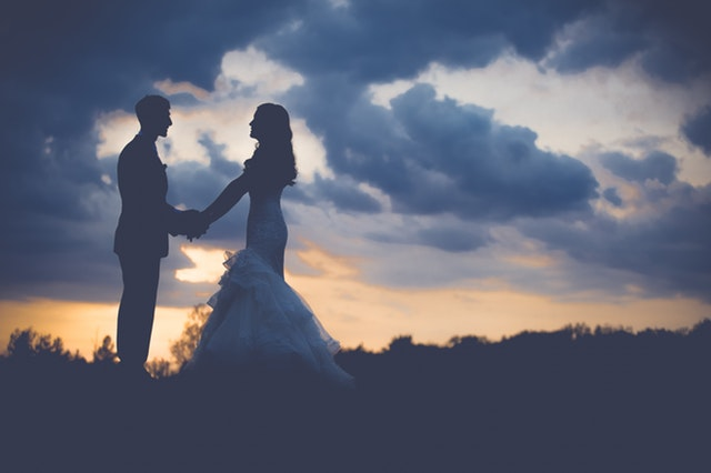 Bride and groom stand under a sunset