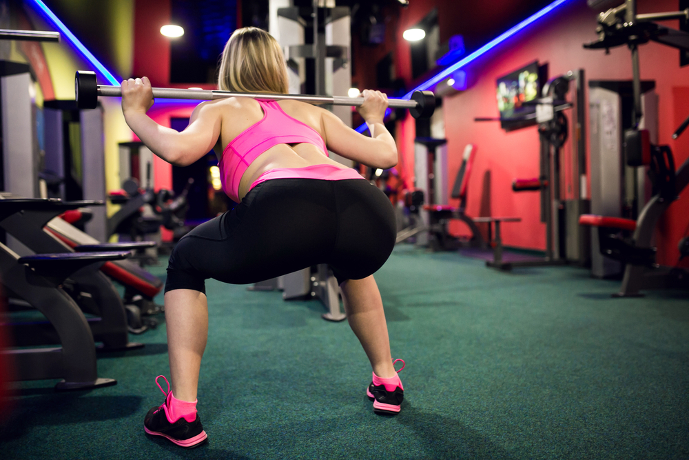 Woman squatting at the gym.