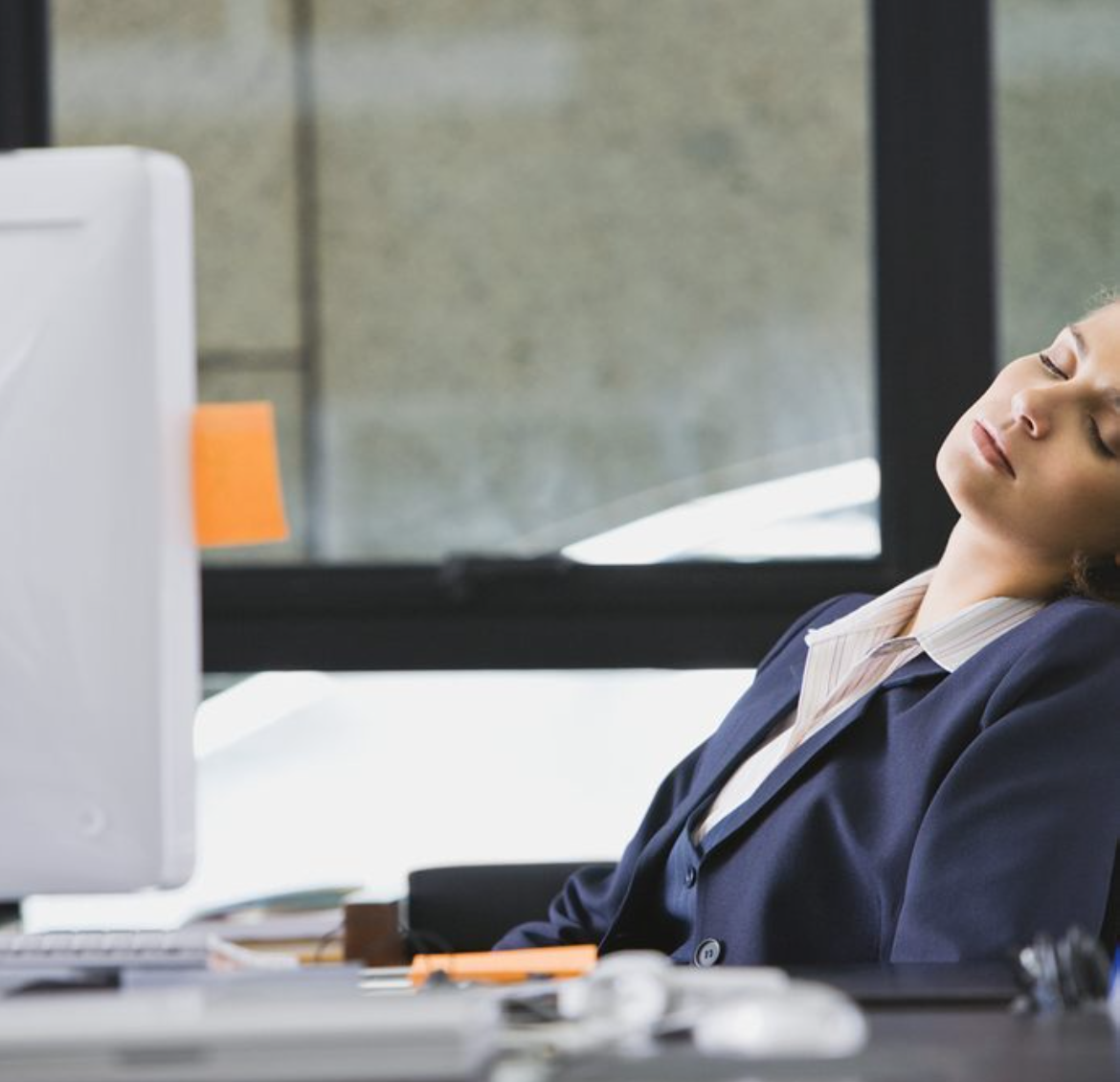 A woman takes a nap at her desk