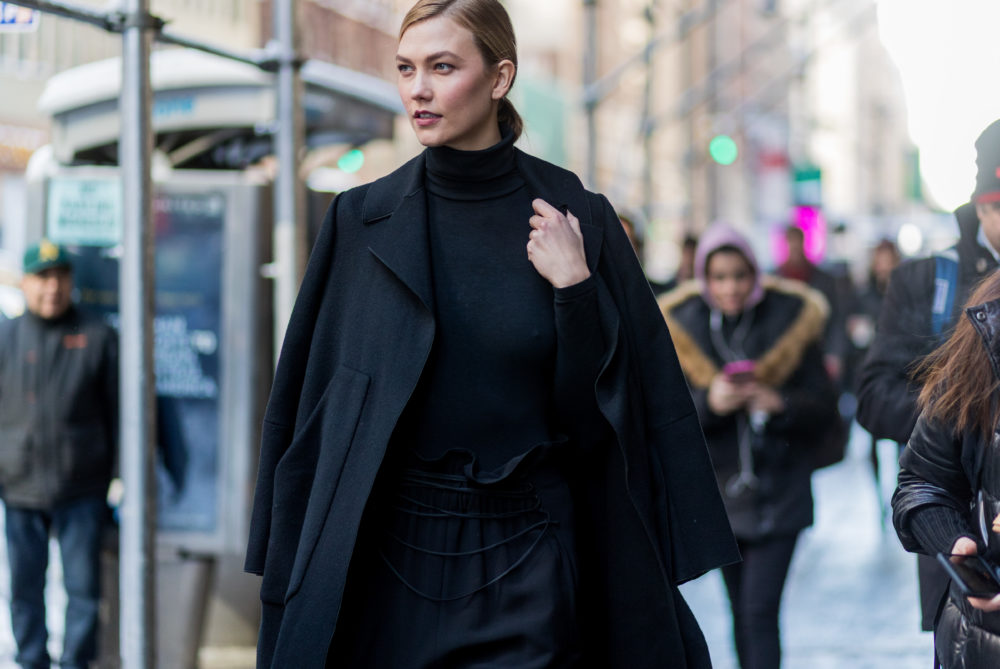 Model Karlie Kloss wearing a black coat, black turtleneck, black jogger pants outside Calvin Klein