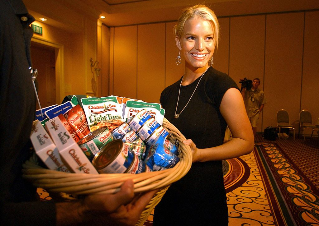 DEL MAR, CA - OCTOBER 20: Pop star Jessica Simpson stands with a basket of tuna products during a visit to a Chicken of the Sea conference at the Marriot Hotel October 20, 2003 in Del Mar, California. Simpson made an earlier statement about chickens not living in the sea which has recently landed her much press. Conference officials taught her the Chicken of the Sea song and gave her a brief history lesson about the company and how they came up with their name. (Photo by Sandy Huffaker/Getty Images)
