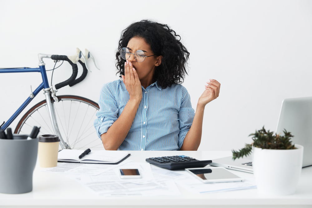 Woman yawming at her desk.
