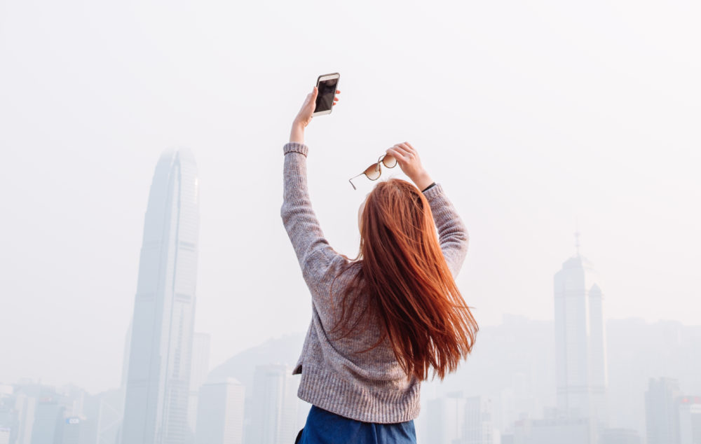 Pretty young lady holding up the smartphone taking selfies herself while holding the shades on the other hand in the promenade, with Hong Kong cityscape skyscraper view in front of her.