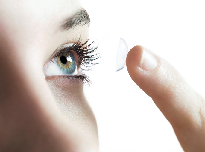Contact lens use. Woman putting in a contact lens.