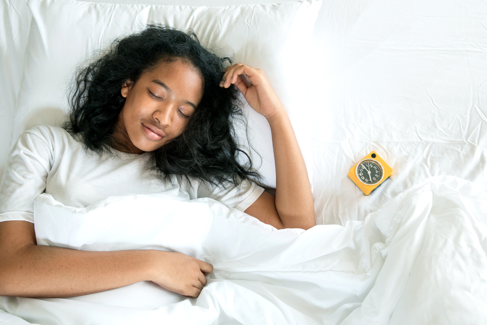 Girl sleeping with alarm clock