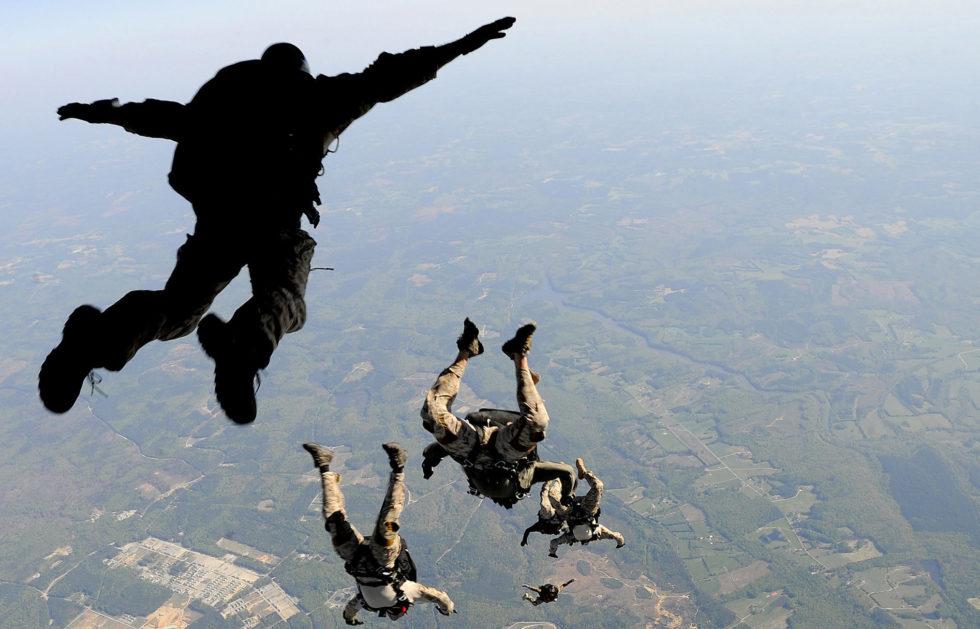 Navy SEALs jump from the ramp of a C-17 Globemaster III over Virginia.