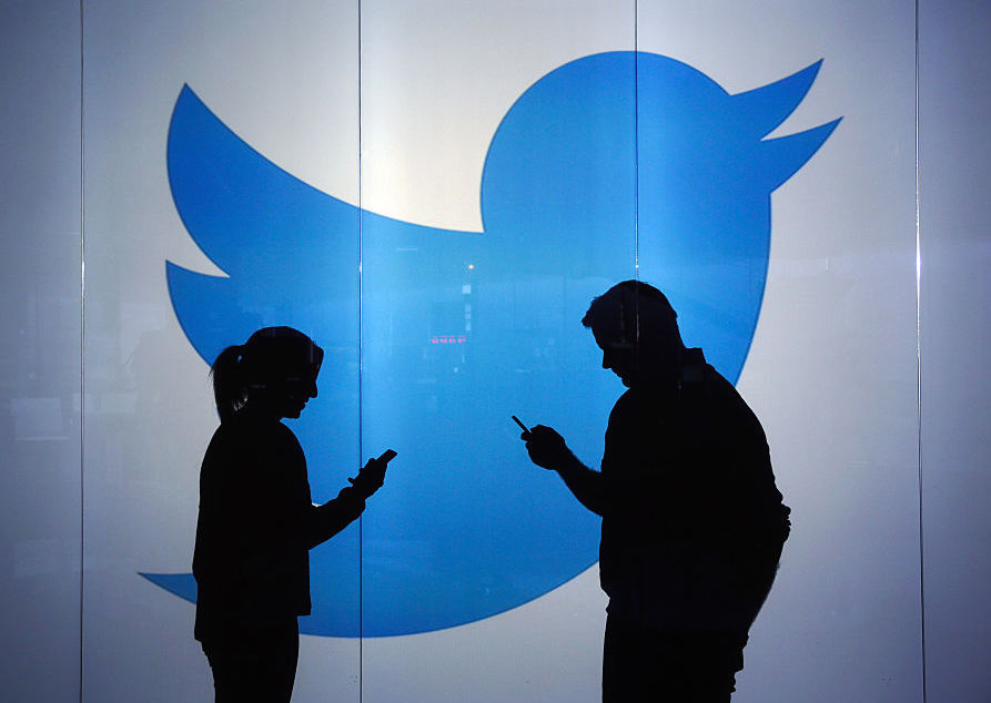 Two people seen as silhouettes as they check mobile devices while standing in front of the Twitter logo
