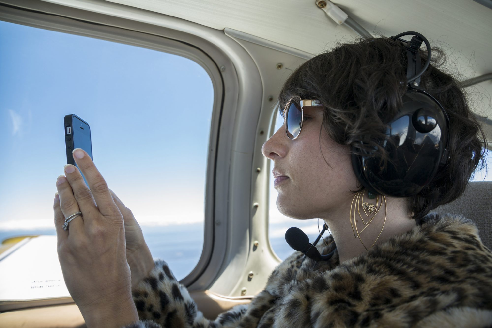 A woman takes a photo with her cell phone during a private flight on a small airplane.
