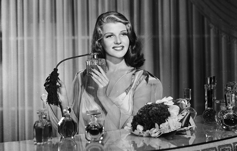 American film actress, dancer and singer Rita Hayworth (1918 - 1987) sprays herself with perfume at a dressing table.