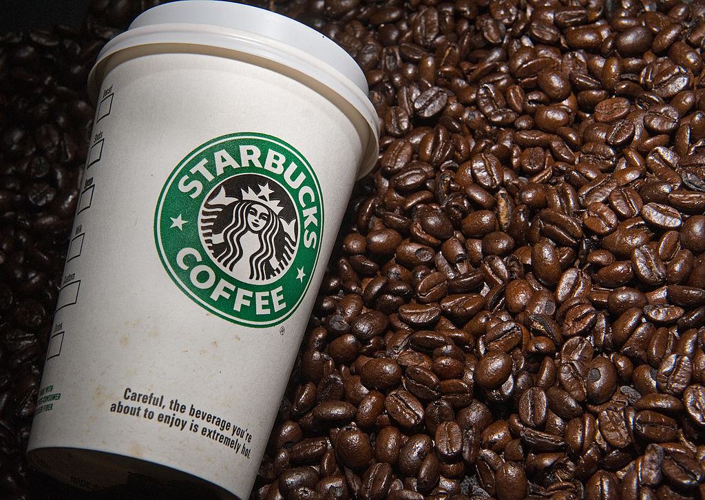 A Starbucks coffee cup and coffee beans