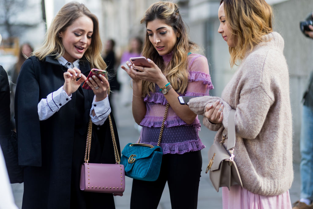 LONDON, ENGLAND - FEBRUARY 18: A group of guests on their phone, texting and talking outside Julien Macdonald on day 2 of the London Fashion Week February 2017 collections on February 18, 2017 in London, England. (Photo by Christian Vierig/Getty Images)