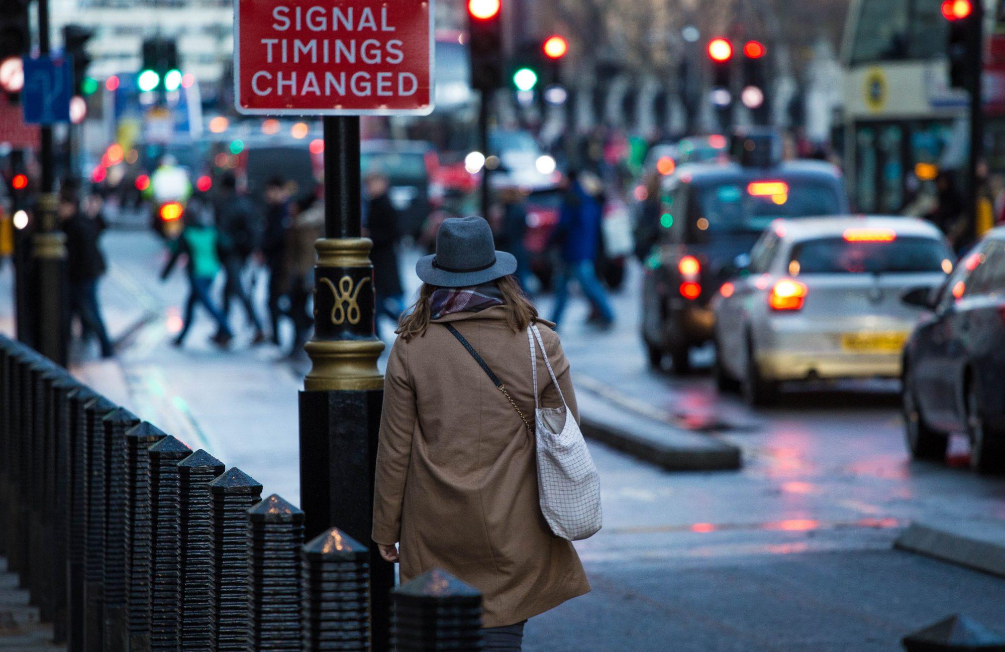 woman-wearing-trench-coat-hat-walking-down-busy-street