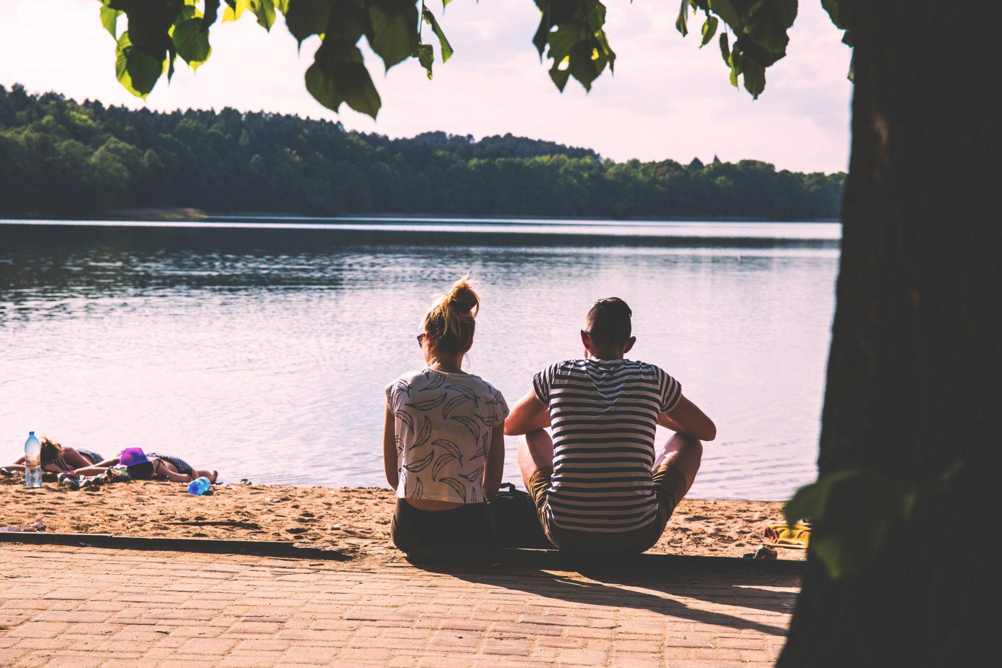 couple-sitting-by-lake