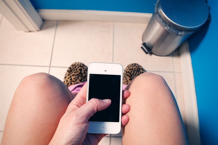 A first person view of a woman texting or scrolling her social media feed as she sits down in a restroom.