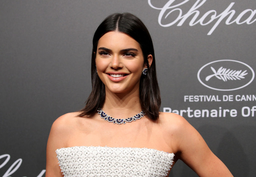 Kendall Jenner wears a white dress and diamond necklace on the red carpet