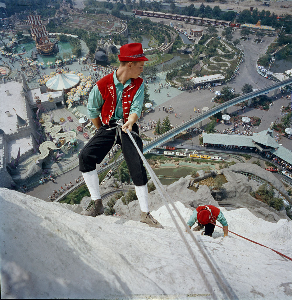 A pair of Disney employees, dressed in a version of traditional Swiss clothing, climb the 'Matterhorn' at the Disneyland Amusement Park. Anaheim, California, 1960.