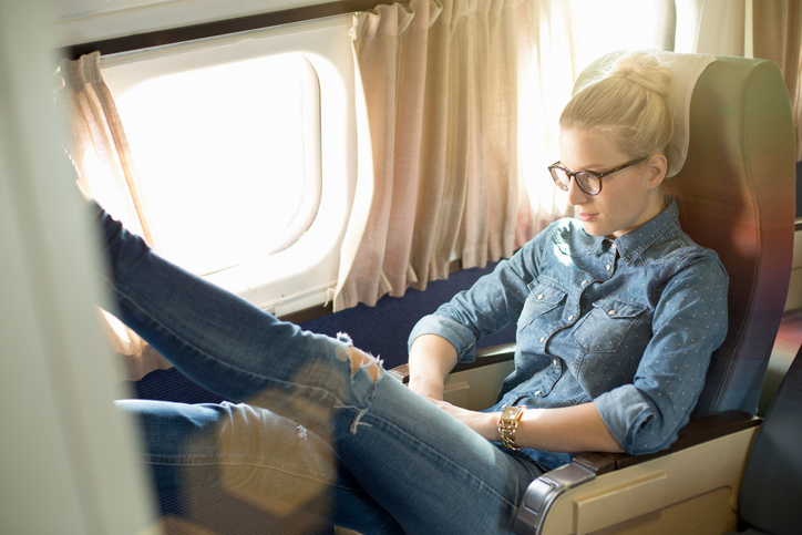 Portrait of young woman sitting on train with feet up