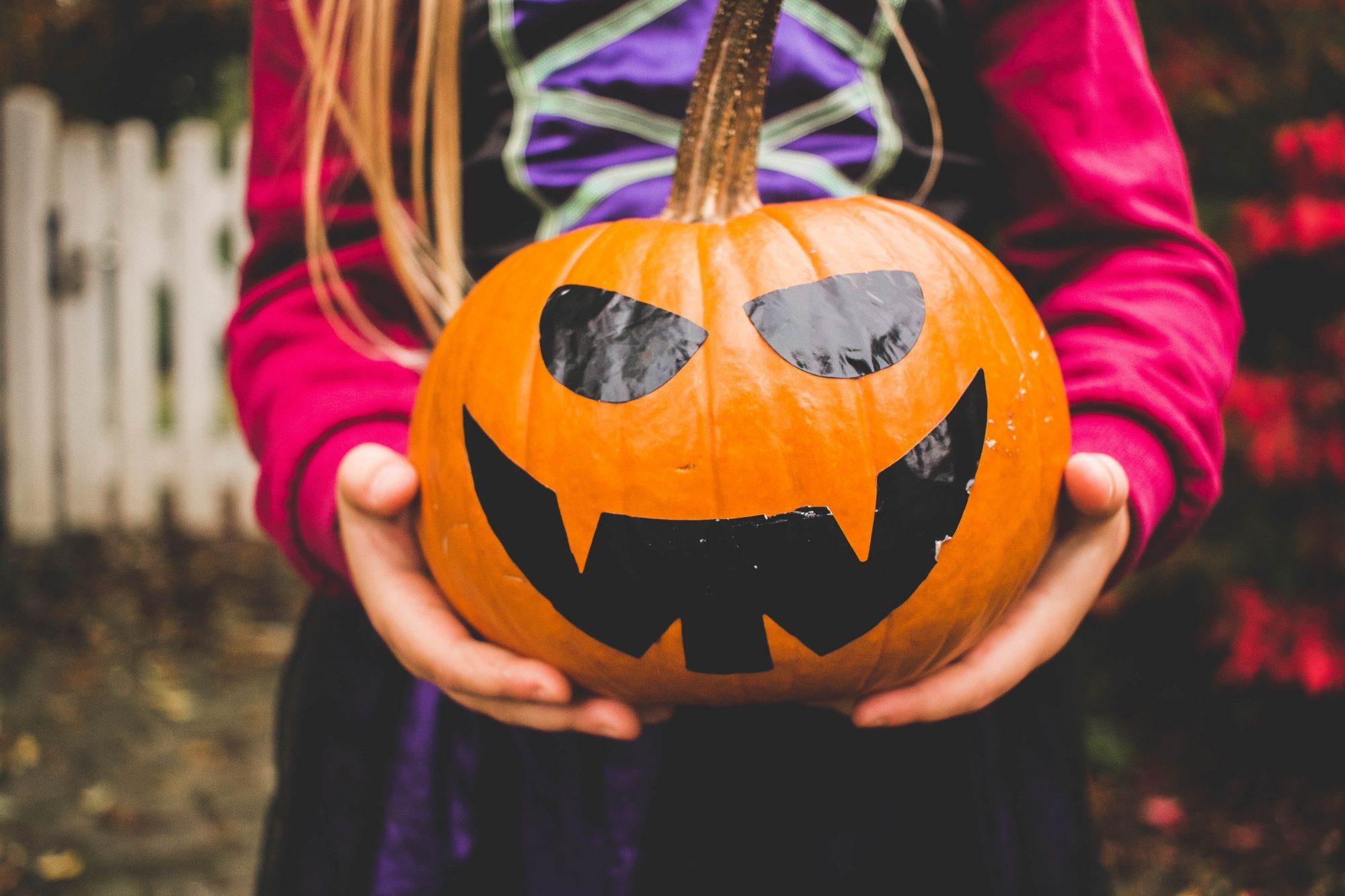 child-holding-decorated-pumpkin
