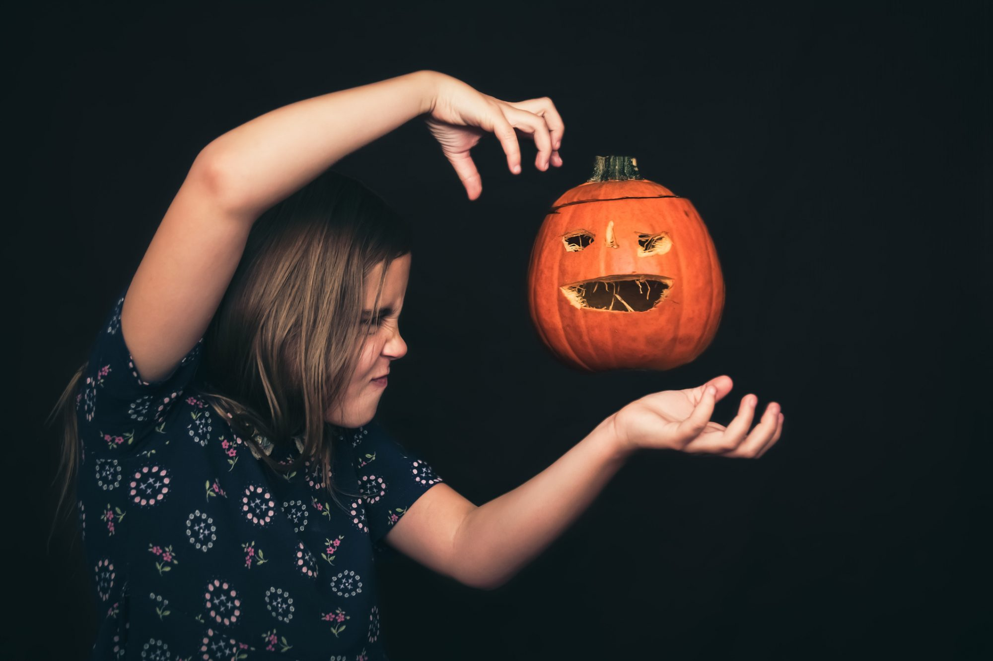A girl concentrates with all her strength as she levitates a jack-o'-lantern.