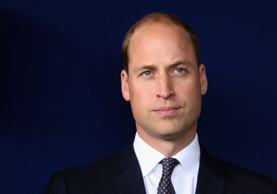 Prince William stands against a dark background