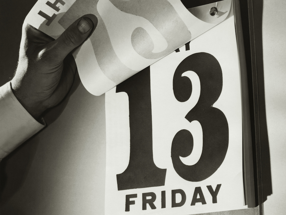 Close-up of a person's hand holding a calendar day sheet and flipping to Friday the 13th