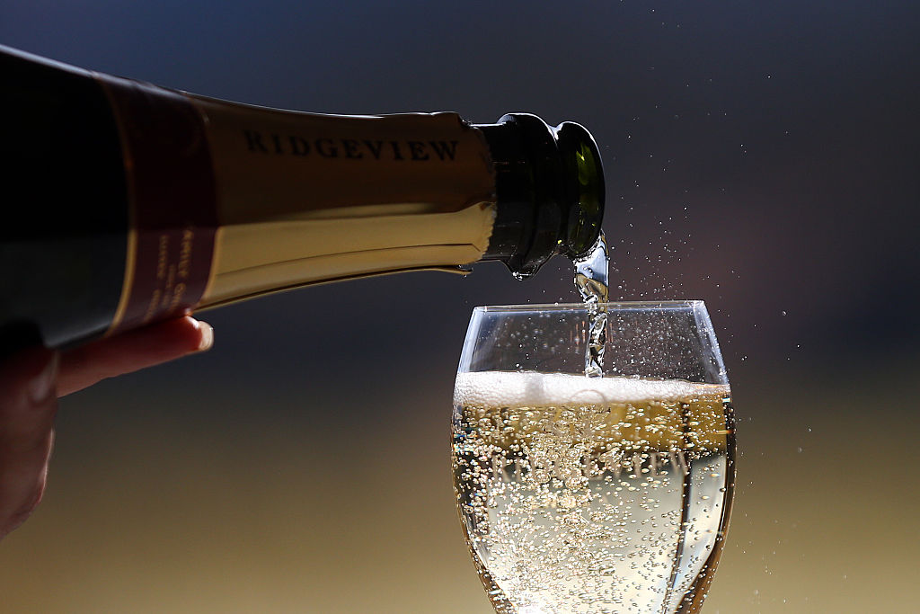 A sparkling white wine is poured from a bottle into a wine glass.