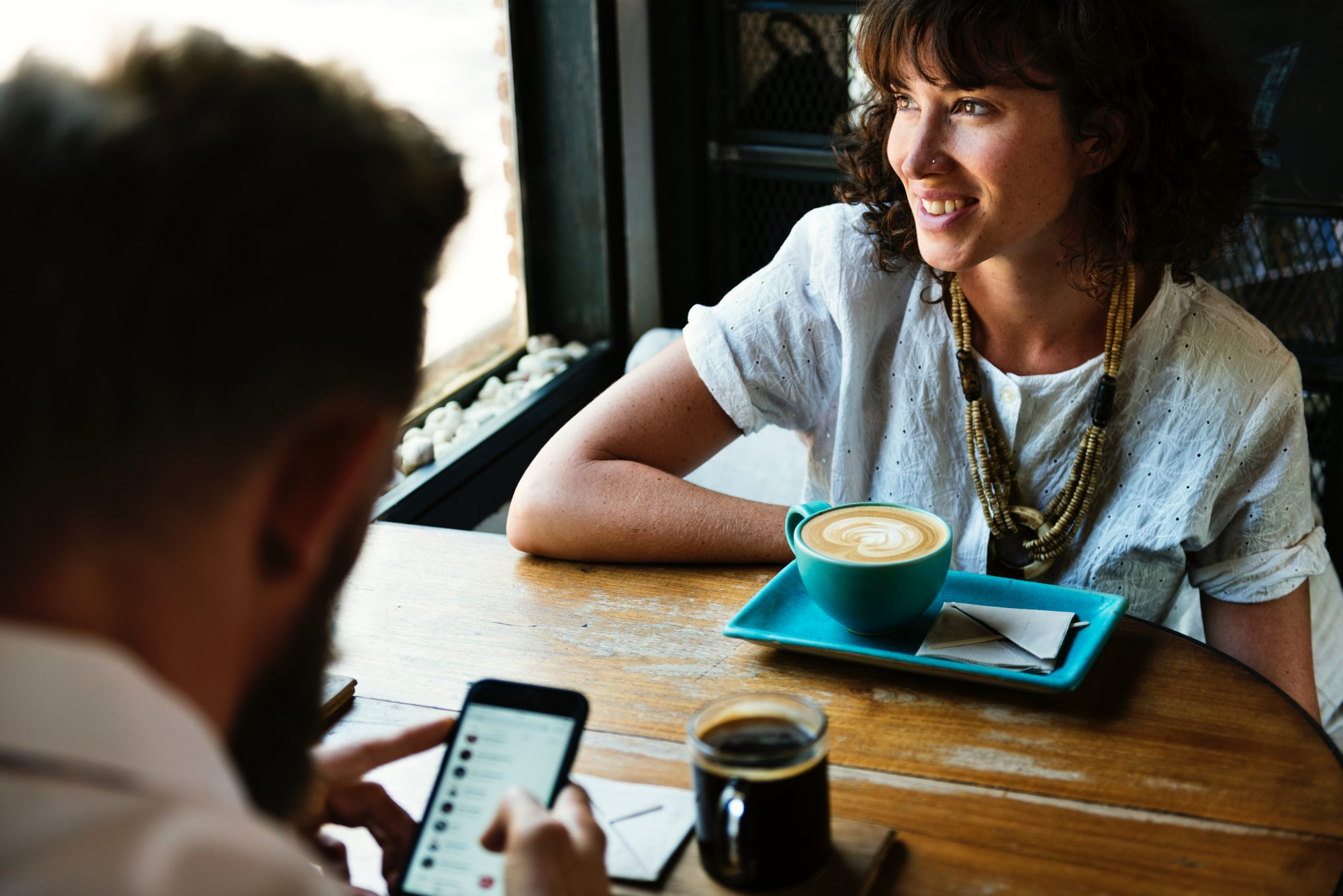 woman-with-cup-of-coffee-sits-across-from-date
