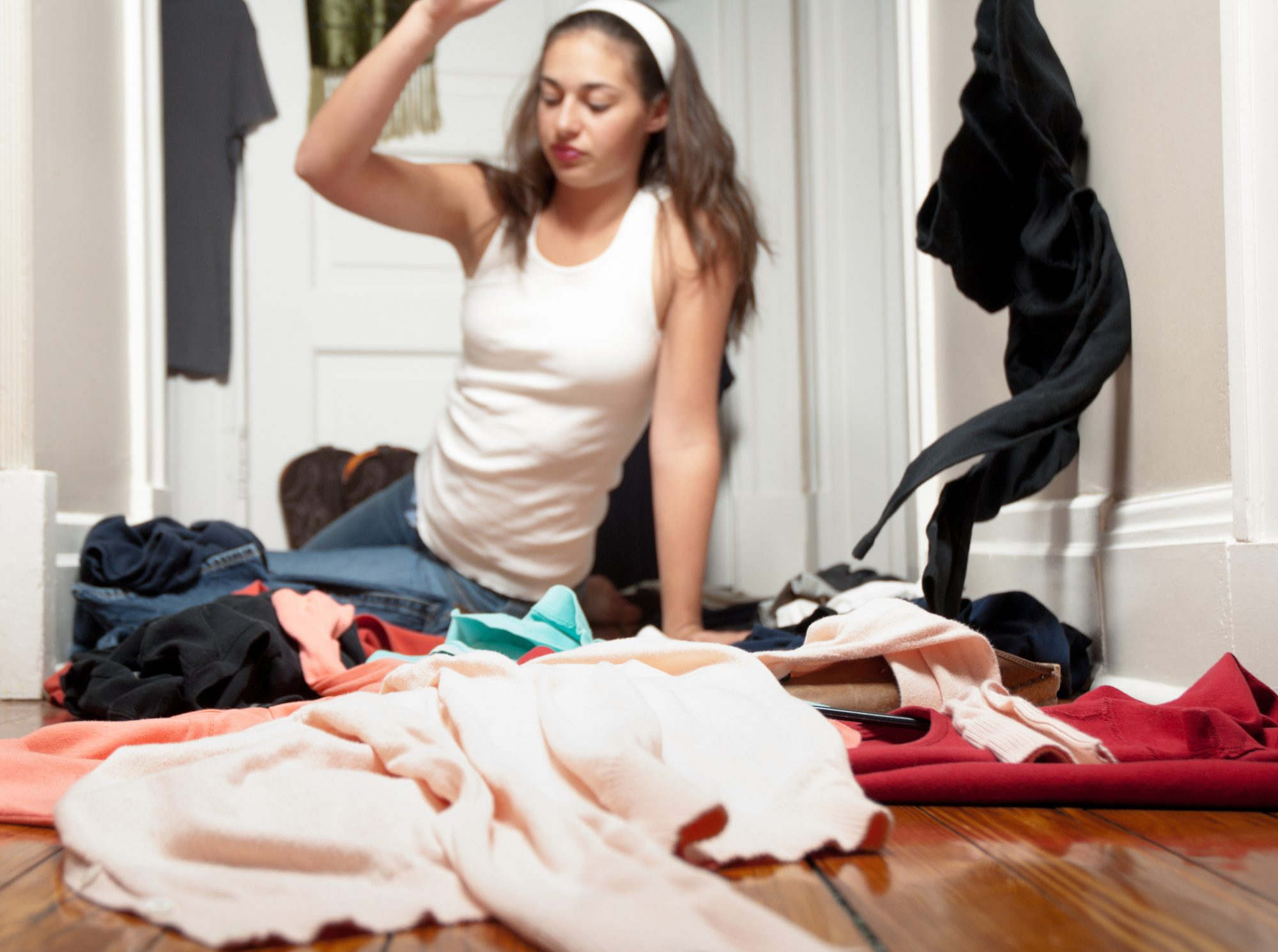 A stock photo of young woman cleaning out her closet