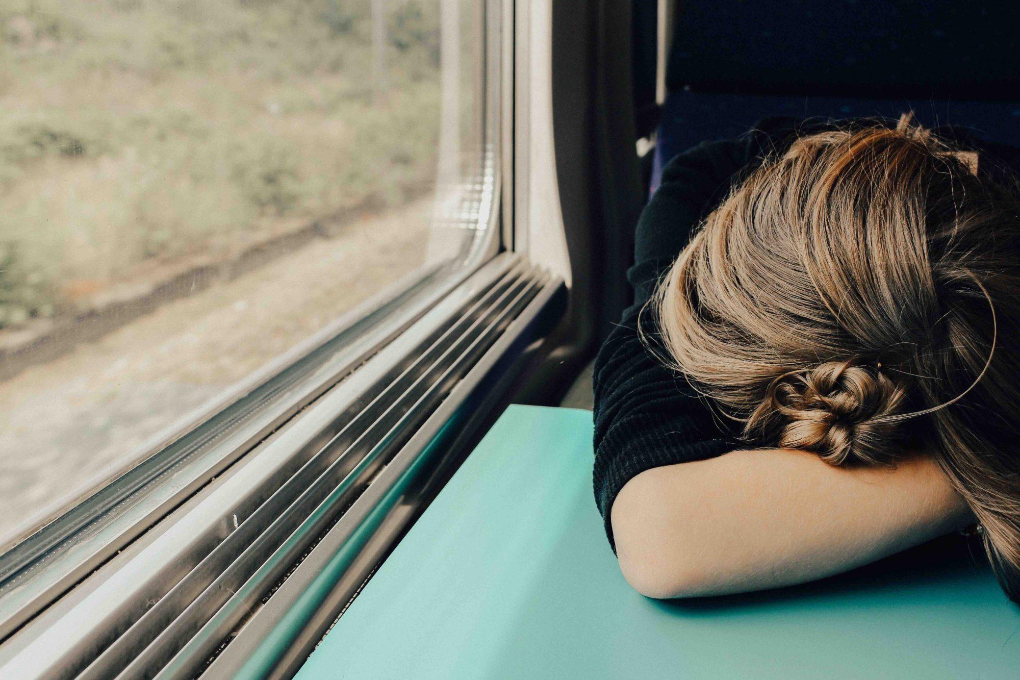 woman-sleeping-on-train-window