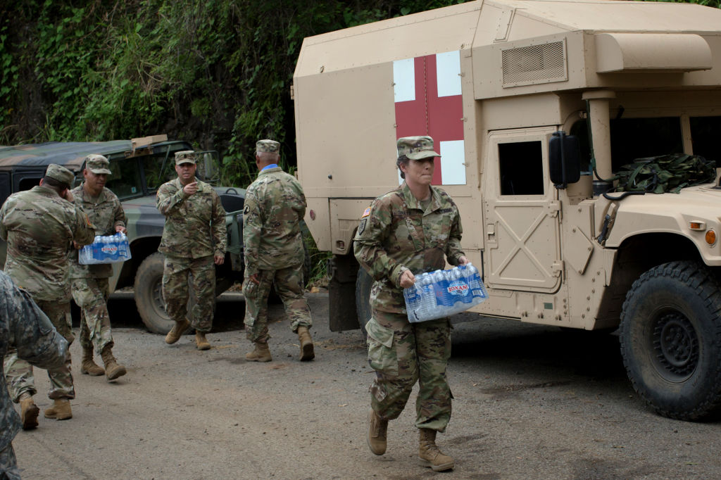 Soldiers assigned to the 1st Mission Support Command, U.S. Army Reserve, move cases of bottled water while working to clear roads of debris near Adjuntas, Puerto Rico, on Saturday, Oct. 7, 2017. U.S. lawmakers pledged to back Puerto Rico's recovery as Governor Ricardo Rossello prepares to ask Congress for a multibillion-dollar aid package to help rebuild from the devastation caused by Hurricane Maria. Photographer: Alex Flynn/Bloomberg via Getty Images
